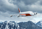 White passenger plane above the mountains — Stock Photo