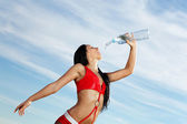 Young female sport girl with a bottle of water — Stock Photo