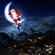 Photo of santa claus sitting on the moon - Stock Photo