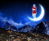 Photo of santa claus sitting on the moon — Stock Photo