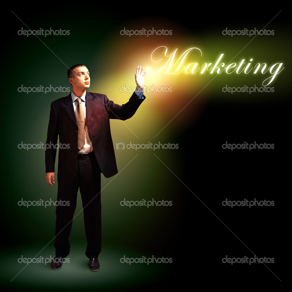 Young successful businessman holding a shining light in his hand as a symbol of success and advancement.  Stock Photo #15774137