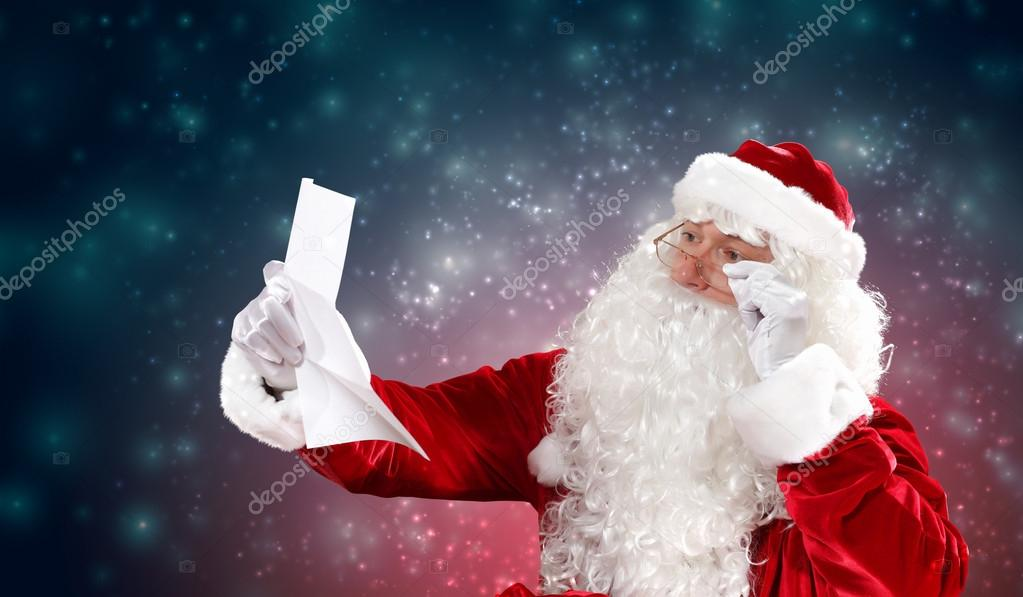 Santa holding Christmas letters and looking at camera — Stock Photo #15774303