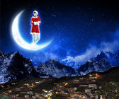 Photo of santa claus sitting on the moon — Stock Photo