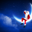 Photo of santa claus sitting on the moon — Foto Stock