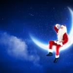 Photo of santa claus sitting on the moon — Stock Photo #16016917