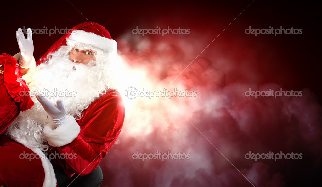 Santa with beard and red hat holding and looking into the sack — Stock Photo #16030855