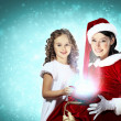 Little girl with christmas gifts and santa — Stock Photo #16244097