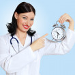 Stock Photo: Young female doctor with clocks