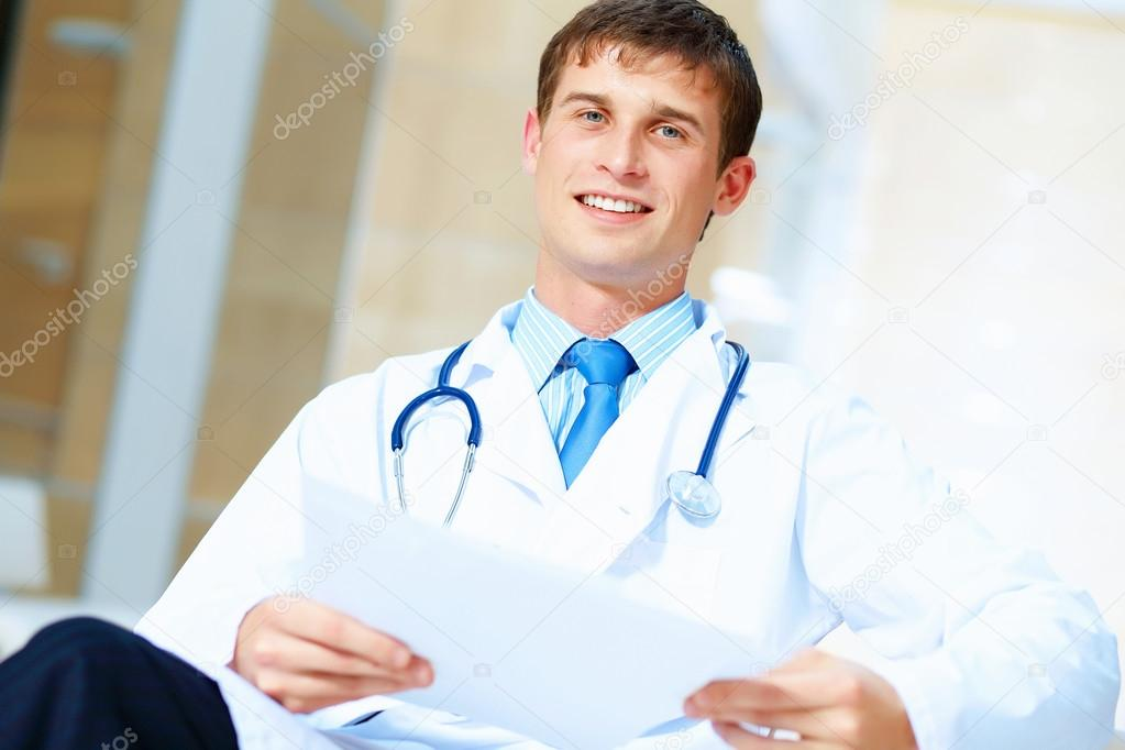 Portrait of friendly male doctor in hospital smiling — Stock Photo #16359273