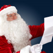Santa claus reading a letter — Stock Photo #16362419