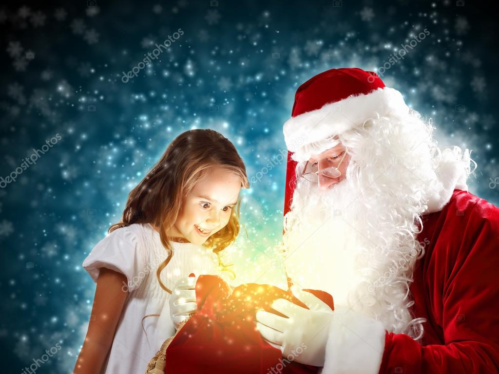 Portrait of Santa Claus with a little girl looking at a gift — Foto Stock #16360891