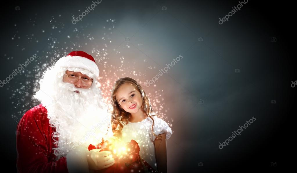 Portrait of Santa Claus with a little girl looking at a gift  Stock Photo #16362643