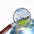Conceptual mini planet with skyscrapers on it under a magnifying glass — Stock Photo