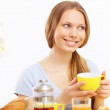 Beautiful young woman drinking tea from yellow cup — Stock Photo