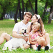 Young Family Outdoors in summer park with a dog — Stock Photo