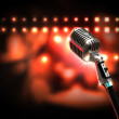 Single retro microphone against colourful background with lights — Stok fotoğraf #19581095