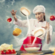 Stock Photo: Asian female cooking with magic against color background