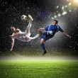 Two football players in jump to strike the ball at the stadium — Stock Photo #19581831