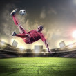 Football player in red shirt striking the ball at the stadium — Stock Photo