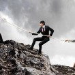 Three businesspeople pulling rope atop of mountain — Stock Photo