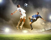 Two football players in jump to strike the ball at the stadium — 图库照片