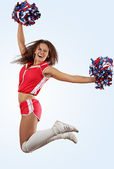 Young beautiful female cheerleader in uniform jumping high — Stock Photo