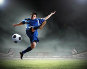 Football player in blue shirt striking the ball at the stadium — Stock Photo
