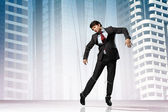 Image of businessman hanging on strings like marionette against city background — Stock Photo