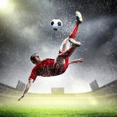 Football player in red shirt striking the ball at the stadium under rain — Stock Photo