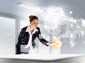 Image of young businesswoman clicking icon on high-tech picture — Stock Photo