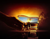 Hand holding one of two glasses of whiskey with nature illustration — Stock Photo