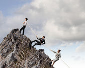 Image of three businesspeople pulling rope atop of mountain — Stockfoto