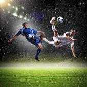 Dwóch piłkarzy w skoku do strajku piłkę na stadionie — Zdjęcie stockowe