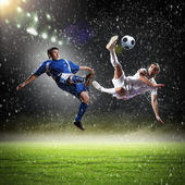Two football players in jump to strike the ball at the stadium — Stok fotoğraf