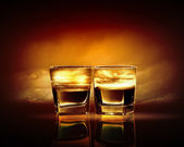 Two glasses of whiskey with sea illustration in against sky background — Stock Photo
