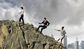 Image of three businesspeople pulling rope atop of mountain — Stock Photo
