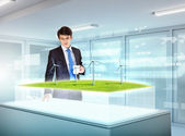 Young businessman looking at high-tech picture of windmills — Stock Photo