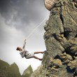 Businesswoman climbing mountain - Stock Photo