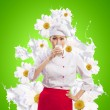 Asian female cook against milk splashes — Stock Photo #21079399