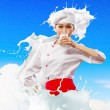 Asian female cook against milk splashes — Stock Photo