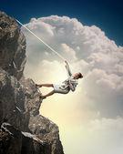 Businesswoman climbing mountain — Stock Photo