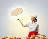 Asian female cook making pizza — Stock Photo