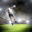 Football player striking the ball - Stock Photo