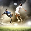 Stock Photo: Two football players striking the ball
