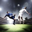 Two football players striking the ball — Stock Photo #21113831
