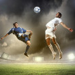 Two football players striking the ball — Stock Photo #21113923