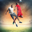 Two football players striking ball — Stock Photo