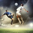 Two football players striking the ball — Stock Photo #21114043