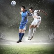 Two football players striking the ball — Stock Photo #21114049