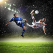 Two football players striking the ball — Stock Photo #21114051